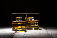 Two glasses of whiskey with ice cubes served on white wooden planks.