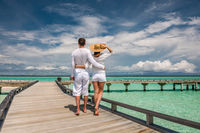 Couple in white on a beach jetty at Maldives