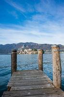 Wooden dock on Lake Orta, opposite the island of San Giulio island with a Benedictine nunnery monastery