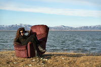 Girl sits on armchair outdoors