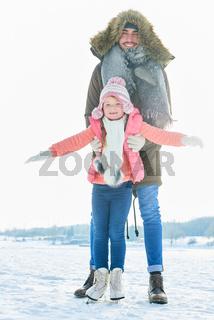 Kind lernt mit Unterstützung Schlittschuh laufen