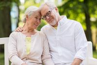 happy senior couple sitting on bench at park