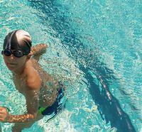 Sweet little boy, swimming in swimming pool, summertime