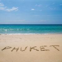 Phuket written on the beach over sea