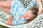 sexy woman is lying in hammock at summer in park