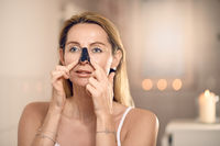 Attractive middle-aged woman applying a face mask