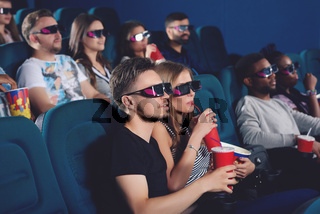 Couple wearing in 3d glasses in modern cinema hall.
