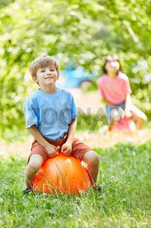 Junge hüpft auf einem Ball im Park