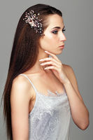 Beauty portrait of young woman. Brunette girl with brooch in long hair and day female makeup on gray background