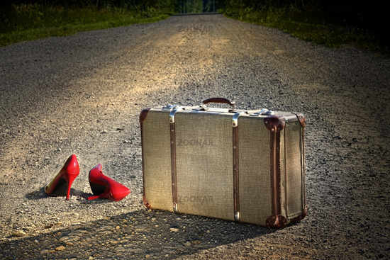 Old suitcase with red shoes left on road