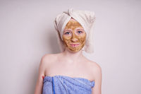 young woman with healing earth or clay beauty facial mask wrapped in towel
