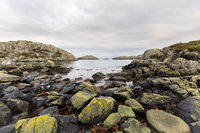 Rocks covered in lichen, the ocean and islands in the background. Urd island at the Rovaer archipelago in Haugesund, norwegian west coast.