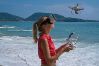 Woan with drone camera and virtual reality glasses taking photos and videos on the beach