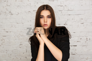 Young fashion model in black jacket next to brick wall