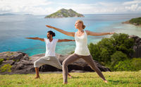 couple making yoga in warrior pose at seaside