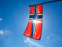 Norwegian flag up close, towards blue sky