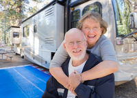 Senior Couple In Front of Their Beautiful RV At The Campground.