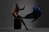 Slim brunette with cloth posing nude on a cube