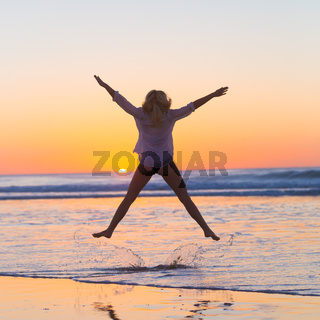 Young beautiful woman jumping in the beach.