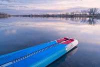 Racing stand up paddleboard on a calm lake