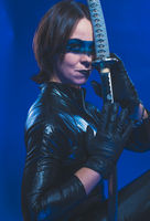 Secret, Brunette girl dressed in leather and latex fitted with japanese swords on blue background