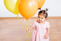happy baby girl with balloons on birthday party