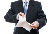 Angry businessman hand tearing paper document