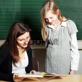 Schülerin und Lehrerin im Klassenraum schauen in ein Schulbuch -quadratisch-