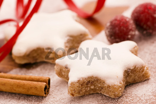 Christmas cookie with rosehip and red robbon as closeup on old wood