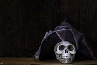 Human skull with magician hat at the wooden wall