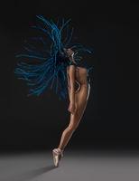 Dreadlocks nude girl in a jump against black wall