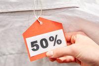 Hand hält Preisschild mit 50% Rabattaktion