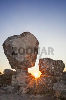 Sun rising between megalithic monument, Montanchez, Spain