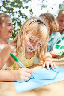 Mädchen malt und zeichnet ein Haus