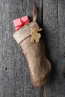 An old fashioned burlap Christmas Stocking hanging on a rustic wood wall. A moose shaped holiday coo