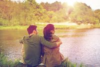 happy couple hugging on lake or river bank