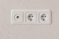 Two electric outlets on wall EU standart and telephone plug.