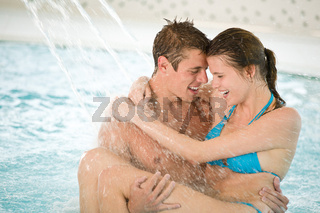 Swimming pool - young loving couple have fun