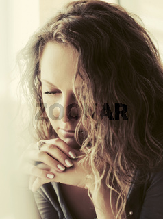 Sad beautiful woman with long curly hairs looking down