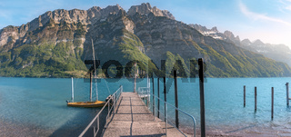 Pier on alpine lake and mountains