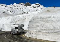 Wohnmobil fährt auf der Passtrasse zwischen hohen Schneemauern über den Gotthardpass
