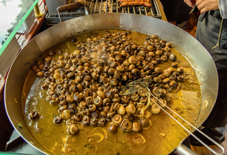 Pan with mushrooms in oil at the Christmas market in Braunschweig, Germany