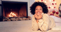 Woman by fireplace and wearing warm sweater