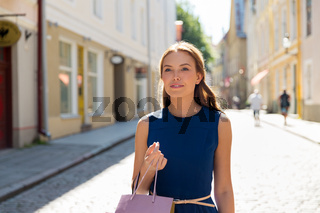 happy woman with shopping bags on city street