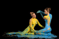 Two nude girls with bodyart sitting on the floor