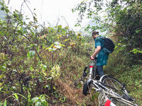 bicyclist on overgrown mountain in Yangshuo