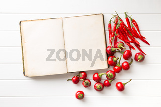 Blank recipe book and hot chili peppers.