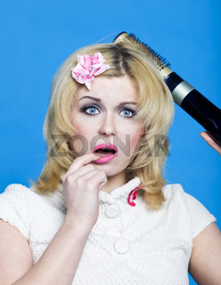 Young blond woman with broken hairdryer