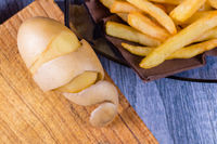 Potato peeled and cutted by hand with knife and french fries at background