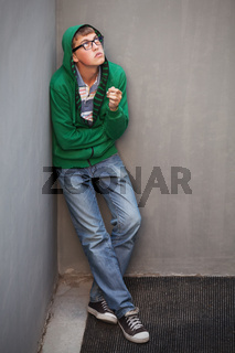 Sad teen boy in depression smoking cigarette at the wall